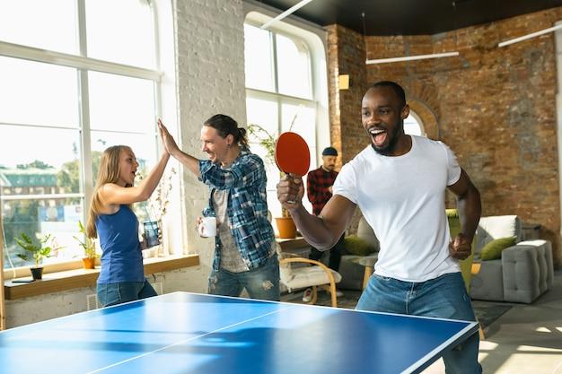 Młodzi ludzie grają w tenisa stołowego w miejscu pracy, dobrze się bawią