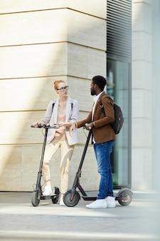 Młodzi ludzie jadący skutery elektryczne w mieście