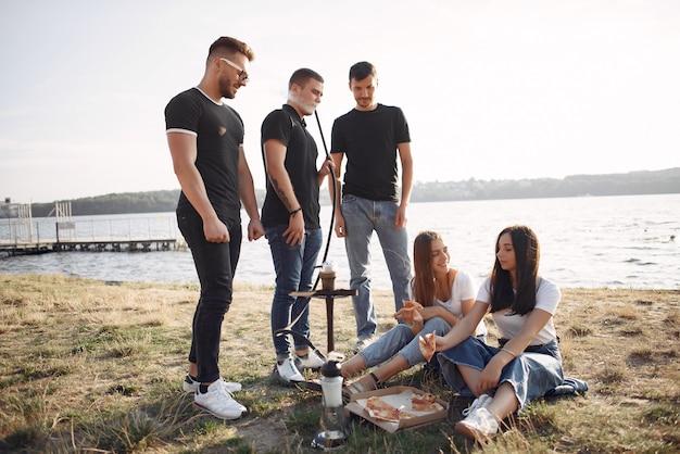Młodzi ludzie jedzący pizzę i palący fajkę wodną na plaży