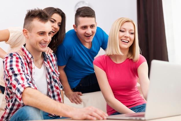 Młodzi ludzie korzystający z darmowej sieci w salonie