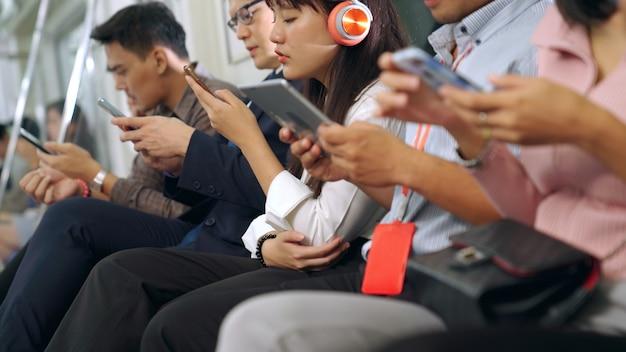 Młodzi ludzie korzystający z telefonu komórkowego w publicznym pociągu metra. miejski styl życia i dojazdy do pracy w koncepcji azji.