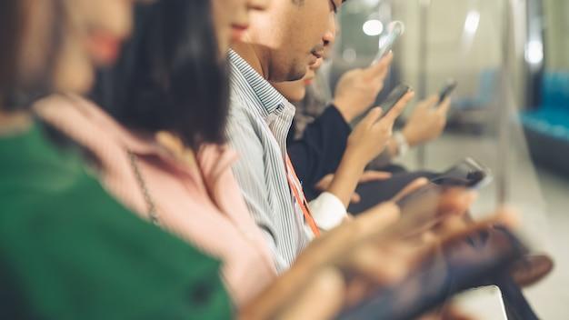Młodzi ludzie korzystający z telefonu komórkowego w publicznym pociągu metra