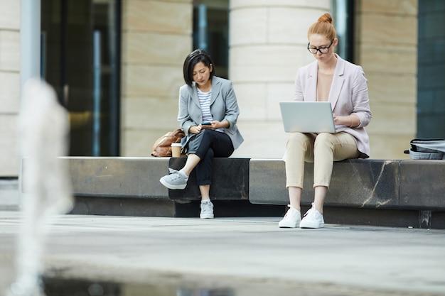 Młodzi ludzie korzystający z urządzeń mobilnych na zewnątrz