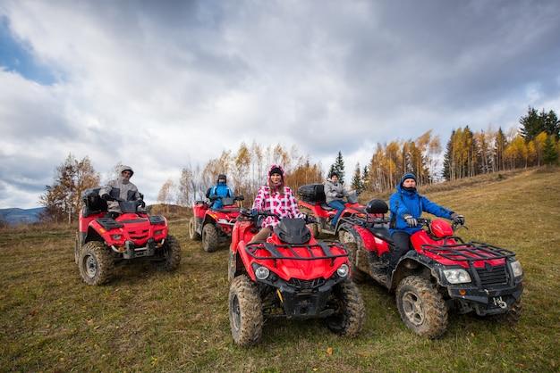 Młodzi ludzie na czerwonych atv terenowych pojazdach na wsi wlec w naturze pod niebem z chmurami