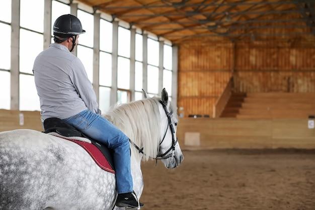 Młodzi ludzie na koniu trenują na drewnianej arenie