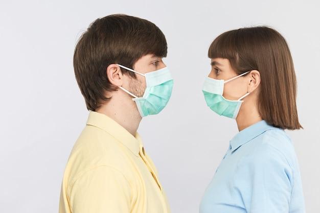 Młodzi ludzie noszący maski ochronne stoją twarzą w twarz, sezon sterylny podczas pandemii koronawirusa
