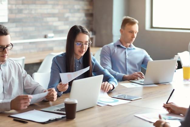 Młodzi ludzie odbywają spotkanie biznesowe w nowoczesnym biurze