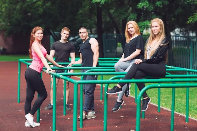 Młodzi ludzie odpoczywają po treningu na boisku sportowym.