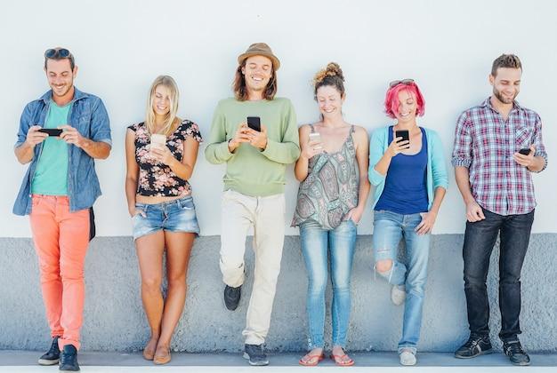 Młodzi ludzie oglądają na swoich inteligentnych telefonach komórkowych, opierając się na ścianie - pokolenie uzależnione od nowych technologii - pojęcie uzależnienia młodzieży od trendów w sieciach społecznościowych
