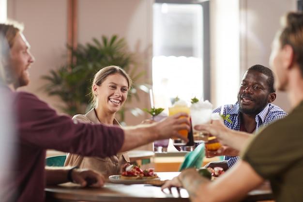 Młodzi ludzie piją koktajle w porze lunchu