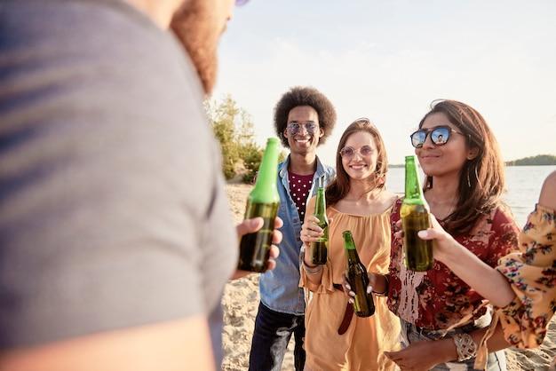 Młodzi ludzie piją piwo na plaży