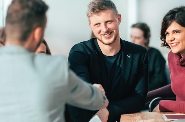 Młodzi ludzie podają sobie ręce na spotkaniu w biurze