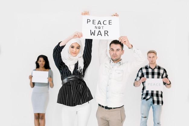 Młodzi ludzie pokazujący hasła pokoju na świecie, przeciwko wojnie i terroryzmowi