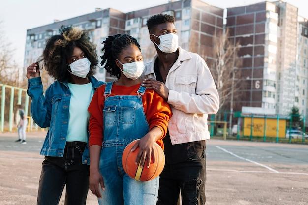 Młodzi ludzie pozuje z medycznymi maskami outdoors