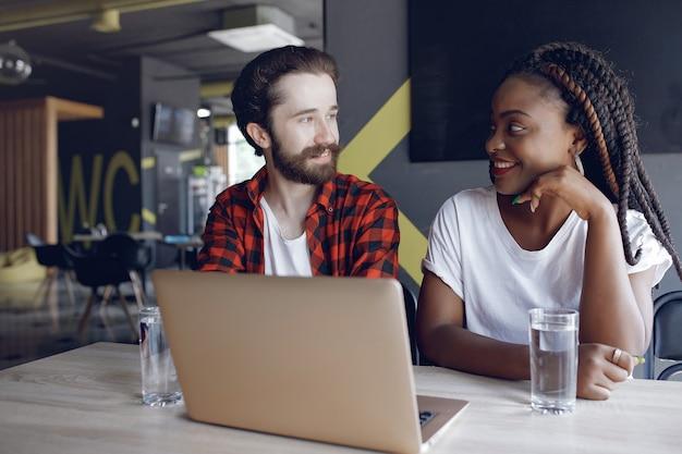 Młodzi ludzie pracujący razem i korzystają z laptopa