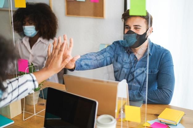 Młodzi ludzie pracujący w coworkingu za pleksi zabezpieczającą podczas wybuchu koronawirusa