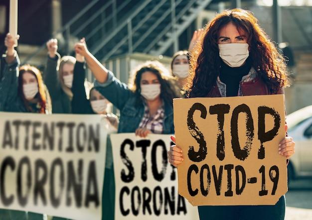 Młodzi ludzie protestują przeciwko pandemii koronawirusa na ulicy. kaukaskie kobiety spotykają się na temat problemów w medycynie, służbie zdrowia, niebezpieczeństwa epidemii. miejsce. zatrzymaj koronawirusa, covid-19.