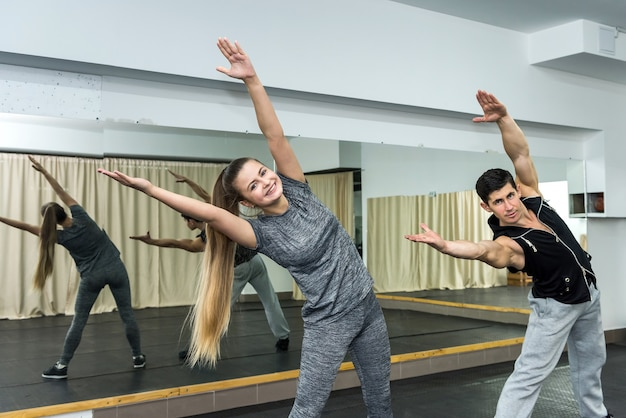 Młodzi ludzie razem wykonują ćwiczenia na siłowni
