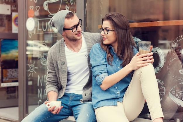 Młodzi ludzie relaks przy filiżance kawy na zewnątrz kawiarni