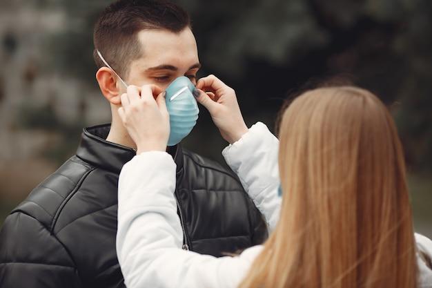 Młodzi ludzie rozkładają jednorazowe maski na zewnątrz