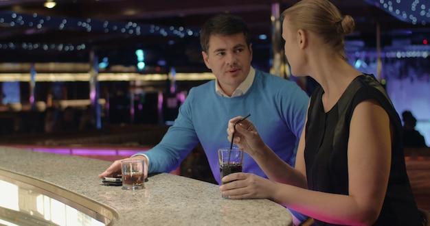 Młodzi ludzie rozmawiają i piją drinki w barze?