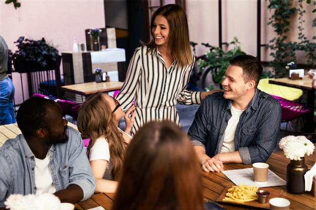 Młodzi ludzie rozmawiają i śmieją się przy stoliku w restauracji na tarasie