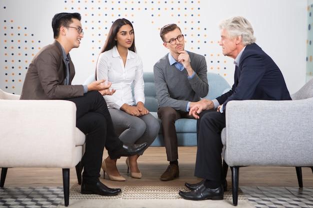 Młodzi ludzie rozmawiają na stanowisko starszego lidera biznesu