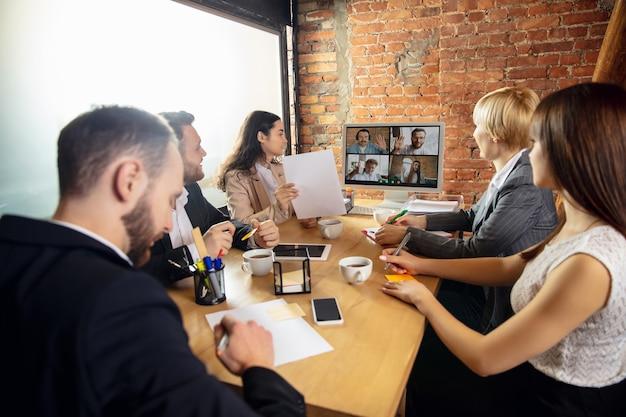 Młodzi ludzie rozmawiają, pracują podczas wideokonferencji z kolegami w biurze lub w salonie
