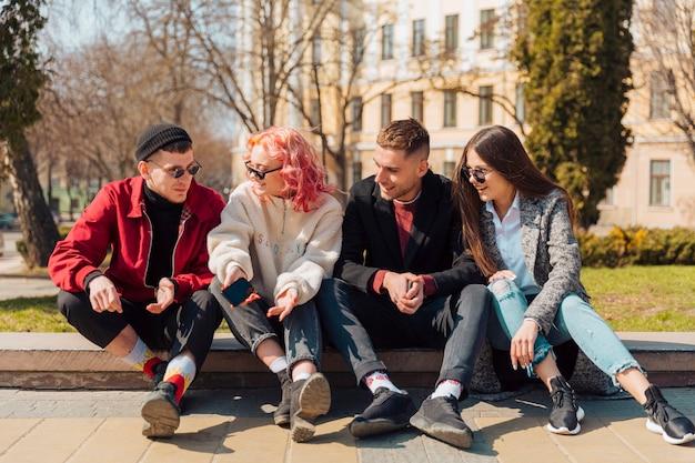 Młodzi ludzie rozmawiają siedząc na krawężniku