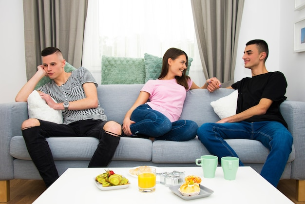 Młodzi ludzie rozmawiający w salonie, zabawna i znudzona koncepcja z różnymi emocjami