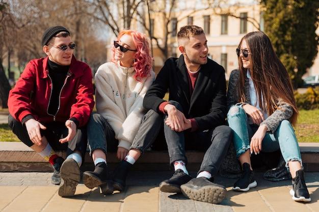 Młodzi ludzie siedzą na krawężniku i rozmawiają ze sobą