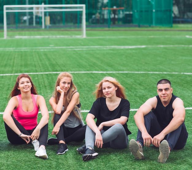 Młodzi ludzie siedzą na trawie na boisku piłkarskim.