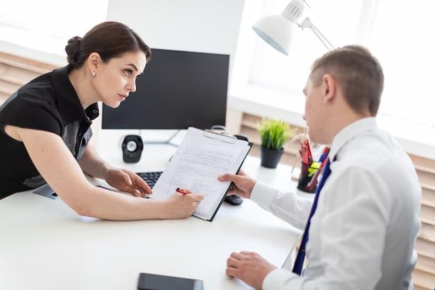 Młodzi ludzie siedzą w biurze przy stole komputerowym i pracują z dokumentami.