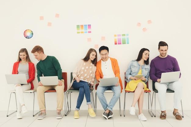 Młodzi ludzie siedzący na krzesłach z gadżetami