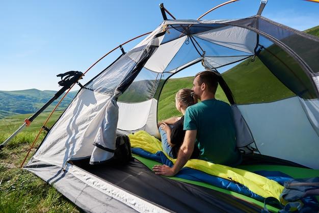 Młodzi ludzie siedzący w namiocie, ciesząc się sobą i górskiej scenerii w słoneczny dzień. w pobliżu namiotu znajdują się kije trekkingowe. koncepcja aktywnego stylu życia na świeżym powietrzu