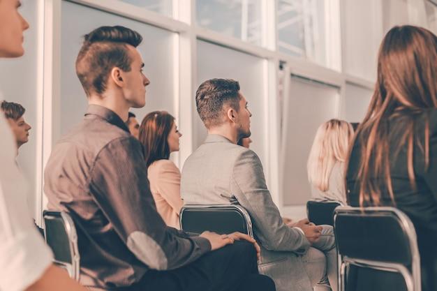 Młodzi ludzie słuchają prelegenta na seminarium biznesowym