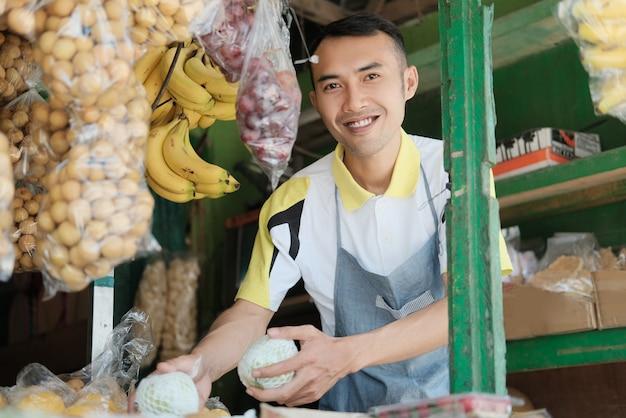 Młodzi ludzie sprzedają człowieka z owocami na rynku owoców