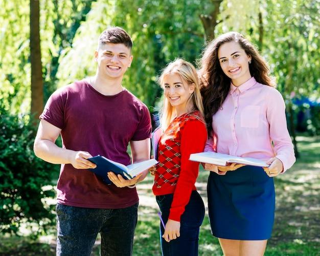 Młodzi ludzie stoi w parku z książkami