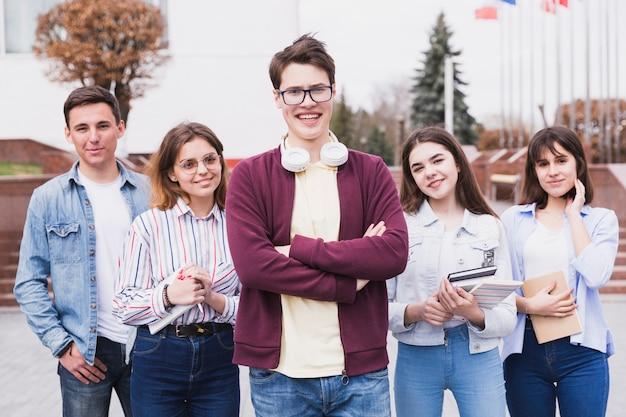 Młodzi ludzie stoi z książkami patrzeje kamerę