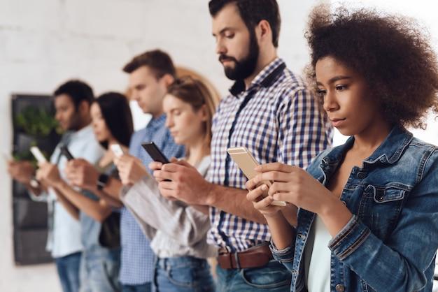 Młodzi ludzie stoją w linii z telefonami komórkowymi.