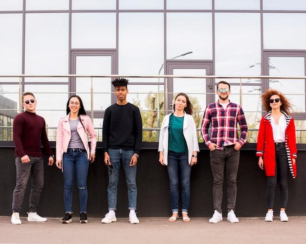 Młodzi ludzie stojący w rzędzie przed szklanym budynkiem