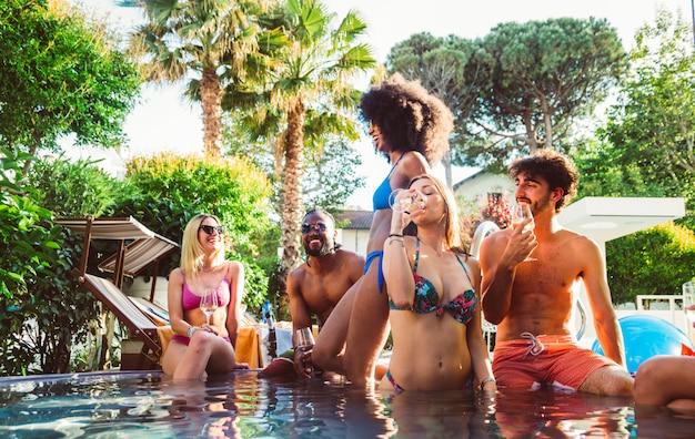 Młodzi ludzie świetnie się bawią na ekskluzywnym przyjęciu przy basenie w tropikalnym kurorcie na wakacjach w lecie