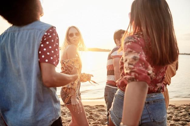 Młodzi ludzie tańczą na plaży