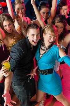 Młodzi ludzie tańczą w klubie lub dyskotece, mężczyźni i kobiety