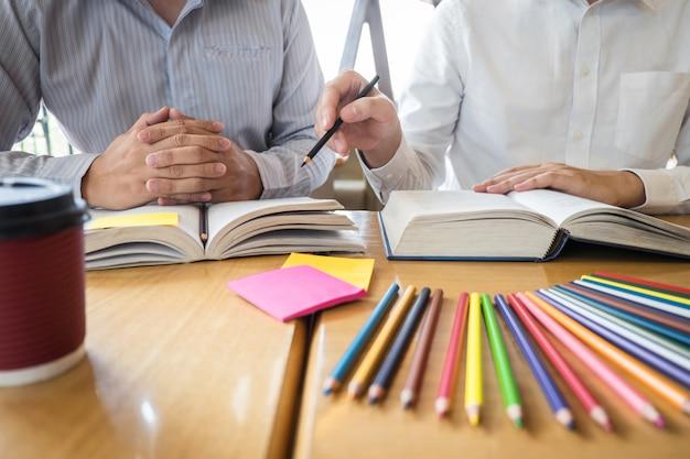 Młodzi ludzie uczący się studiować wiedzę w bibliotece podczas pomocy w nauczaniu przyjaciela przygotowują się do egzaminu
