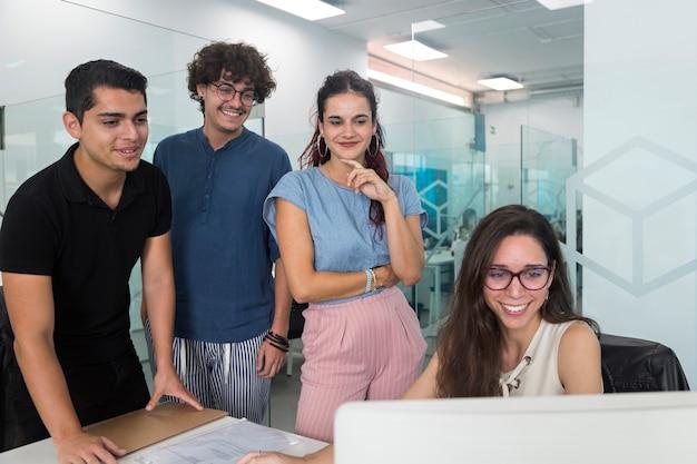 Młodzi ludzie uśmiechnięci i zaskoczeni oglądając komputer w biurze coworkingowym.
