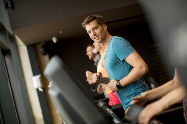 Młodzi ludzie używają threadmill w nowożytnym gym