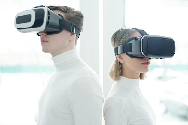 Młodzi ludzie w białych swetrach i goglach wirtualnej rzeczywistości stoją tyłem do siebie