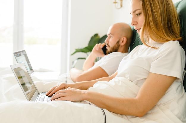 Młodzi ludzie w domu lub tysiącletnia piękna para w hotelu za pomocą połączenia internetowego i urządzeń technicznych, takich jak komputerowy laptop.