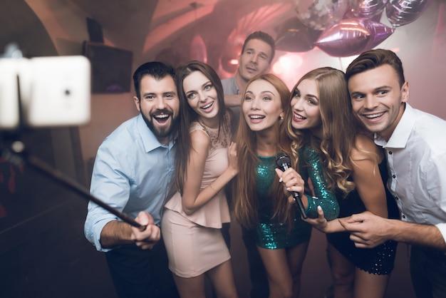 Młodzi ludzie w klubie śpiewają piosenki, tańczą i robią selfie